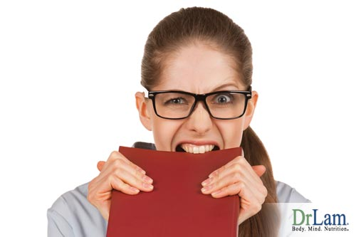 A young woman biting a notebook, looking stressed and dealing with irritability and adrenal fatigue