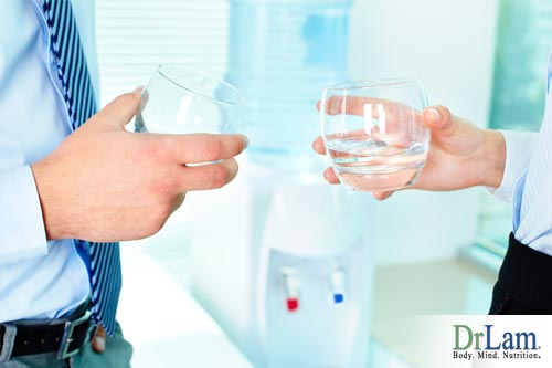 Two people holding glasses of water during a break, making use of one of the tips on how to stay focused
