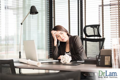A business professional at her computer looking tired with irritability and adrenal fatigue/