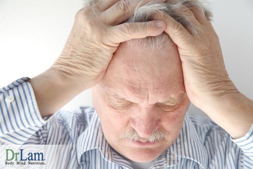 A man grabbing his head looking tired and stressed, suffering from irritability and adrenal fatigue.